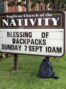 A backpack leans against the church sign advertising the blessing of backpacks.