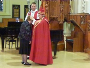 Bishop Michael gives Patty the medal.