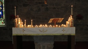 The candles on the altar for Christmas ablaze.